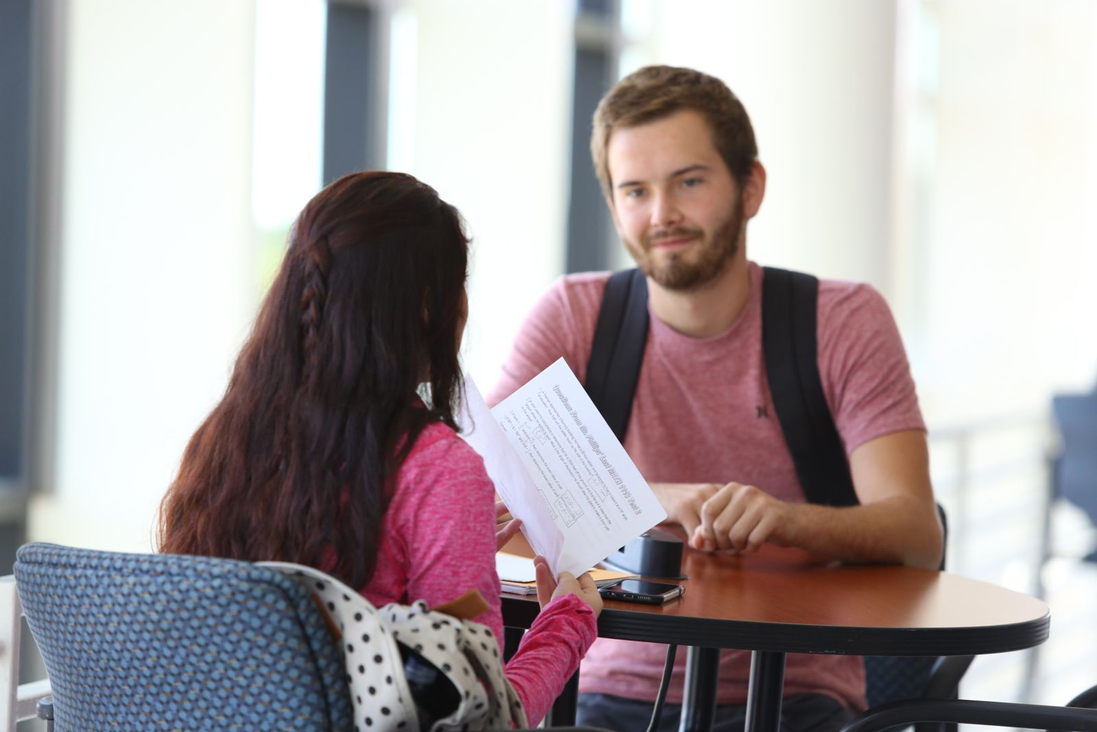 male and female student sitting at a high top tables studying