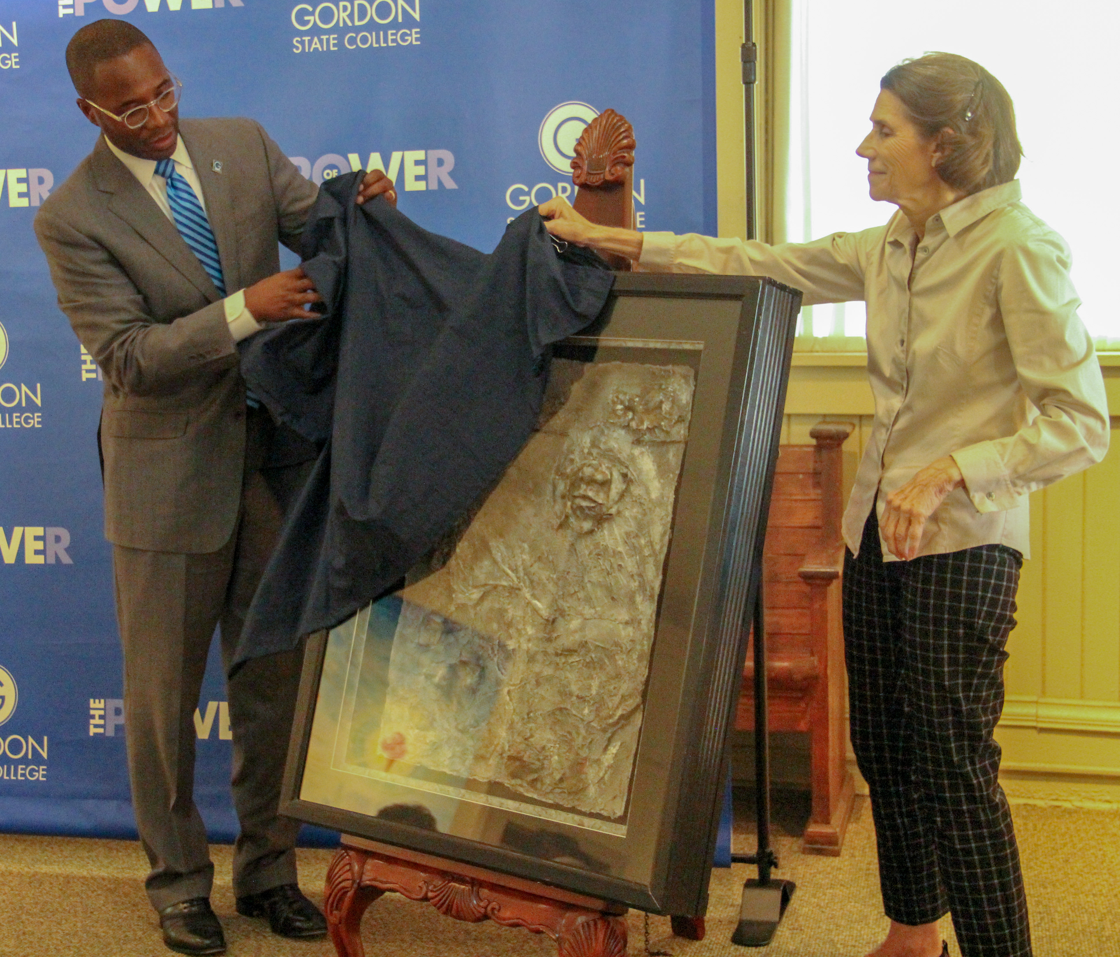 Gordon State College President Kirk A. Nooks and Lamar Arts Depot Gallery Director Angela Preston unveil Virginia Cherry Legge's work.