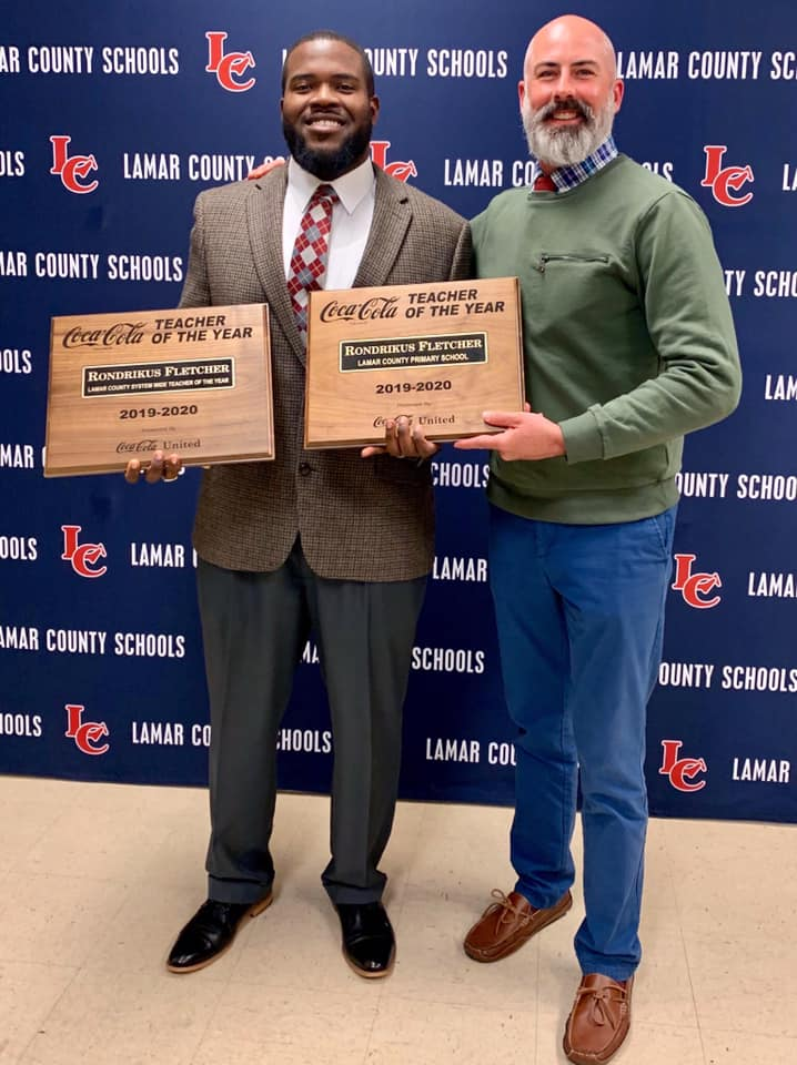 Gordon State College alumnus Rondrikus Fletcher receives Lamar Co. School System Teacher of the Year Award from Principal of Lamar County Primary School Jeremy Hawkins.